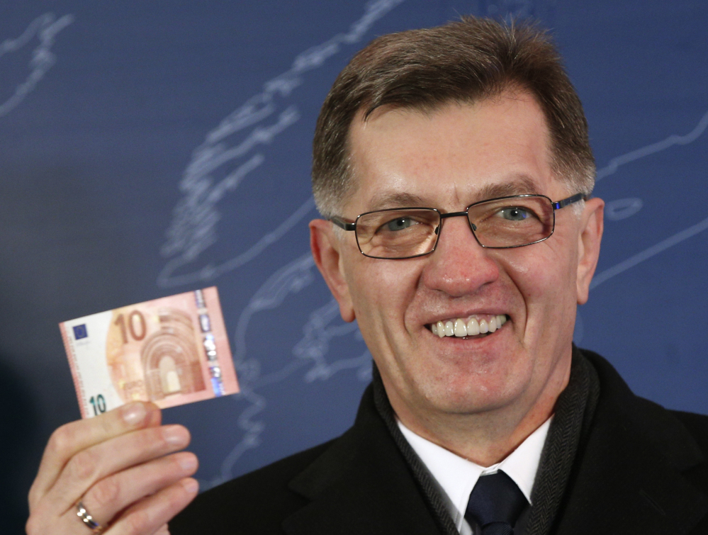 Lithuania's Prime Minister Algirdas Butkevicius holds up a 10 Euro banknote that he withdrew from an ATM cash machine in Vilnius, Lithuania, early Thursday.