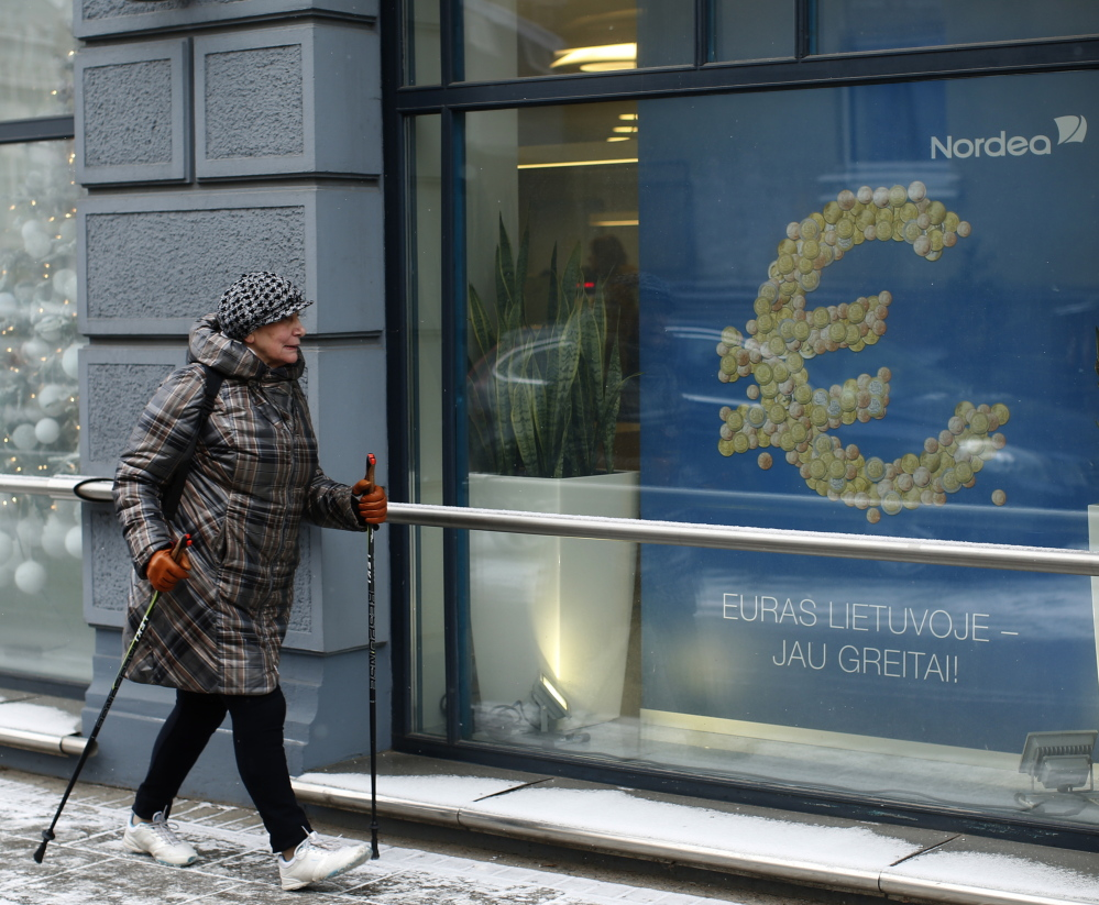 "A woman walks by a poster reading ""The euro is coming to Lithuania soon"" in Vilnius, Lithuania, on Monday. Political leaders are hoping that joining the euro will help Lithuania distance itself further from Russian influence as well as boost the economy."