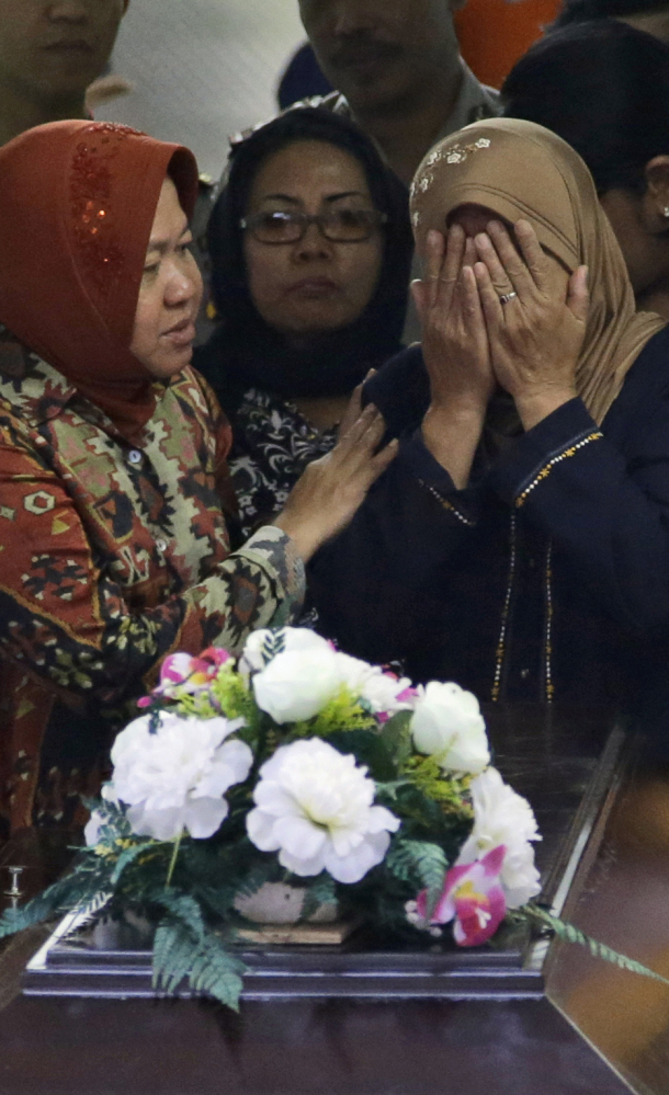 A woman weeps over the casket of AirAsia crash victim Hayati Lutfiah, in East Java, Indonesia, on Thursday.
