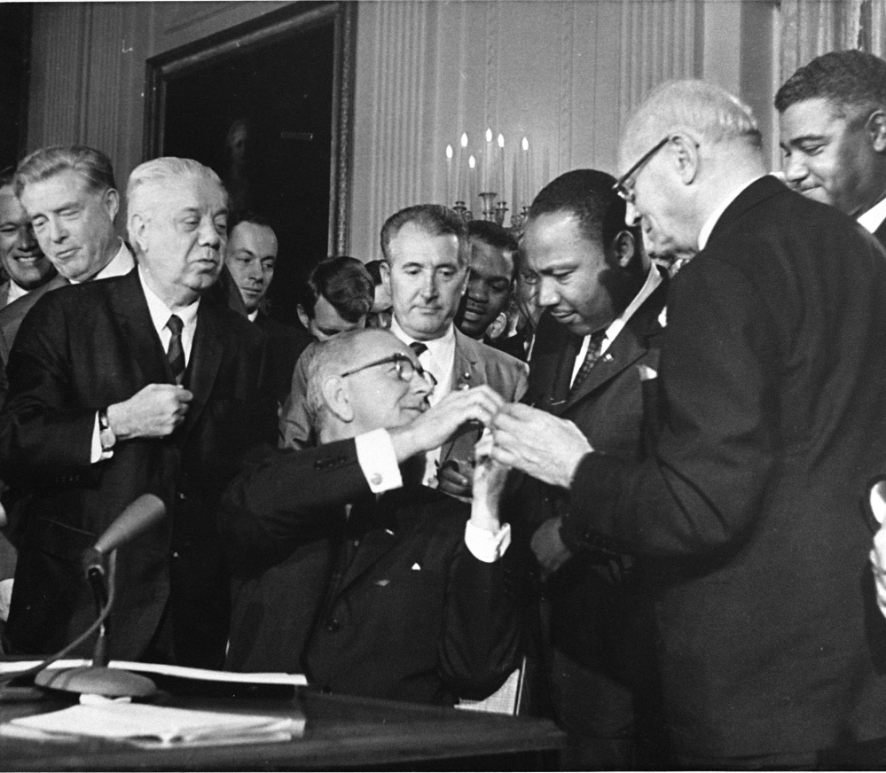 The Rev. Martin Luther King, third from right, head of the Southern Christian Leadership Conference, was among national figures present on July 2, 1964, as President Lyndon B. Johnson, seated, signed the Civil Rights Bill.