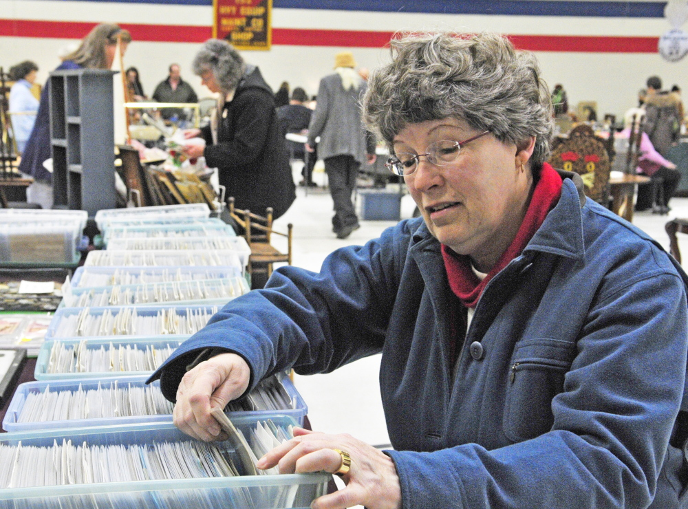 "Mary Saunders flips through postcards Thursday at the 24th annual Augusta Armory Antiques Show. ""I enjoy looking at everything,"" she said."