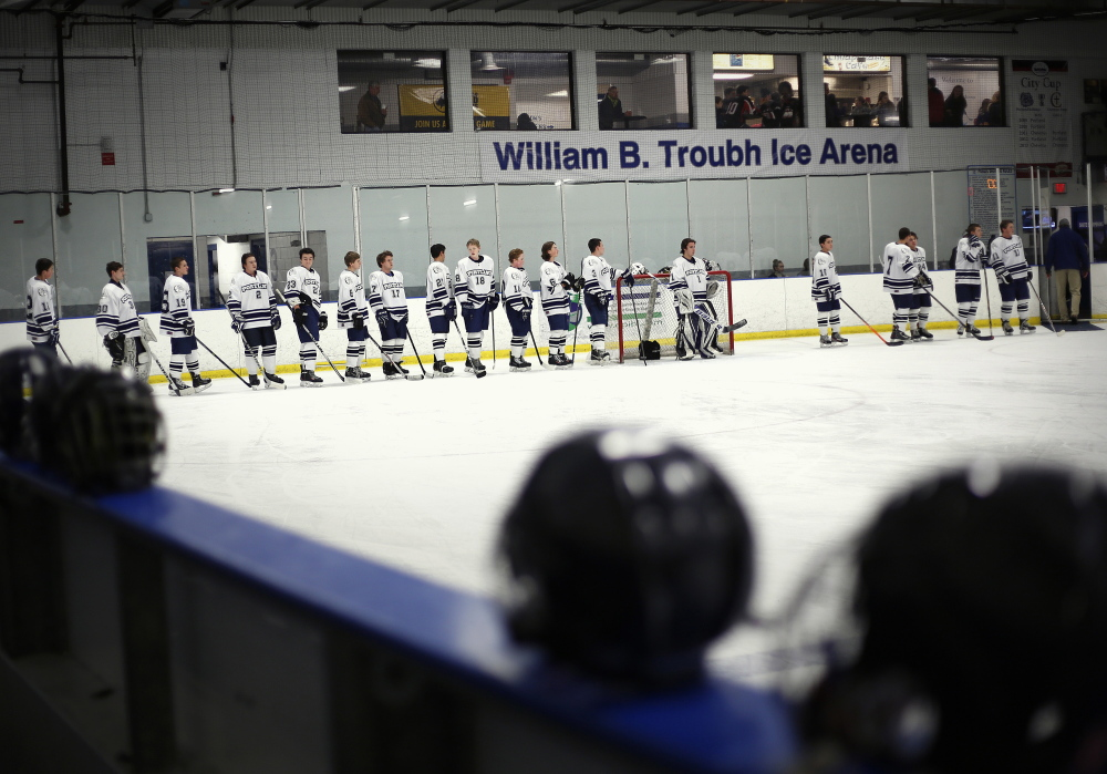 The combined Portland High-Deering High boys' hockey team lines up Thursday before the start of the team's City Cup game against Cheverus, in front of a banner carrying the new name of what was once the Portland Ice Arena. The City Cup series was created to raise hockey's profile in Portland and raise money for the Portland Middle School Hockey Association.