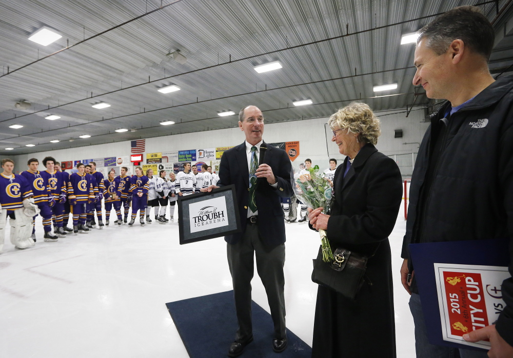 "Jerry Conley, president of the Portland Middle School Hockey Association, presents a plaque to Nancy Troubh, William B. Troubh's widow, and their son, Jed Troubh, before the City Cup. Her husband ""always said he wanted to give back to the city,"" Nancy Troubh said."