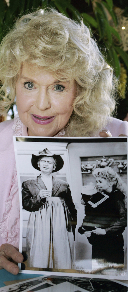 "Donna Douglas, who starred as Elly May Clampett in the television series ""The Beverly Hillbillies,"" holds a publicity photo of herself from the show in Baton Rouge, La., in 2009. Douglas died Thursday at age 82."
