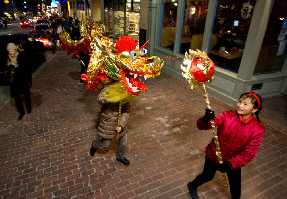 Students from the Chinese & American Friendship Association of Maine Chinese School carry a large dragon along Congress Street on Friday to promote their Chinese New Year celebration, which will take place Feb. 7 at the Westbrook Performing Arts Center. Photos by Gabe Souza/Staff Photographer