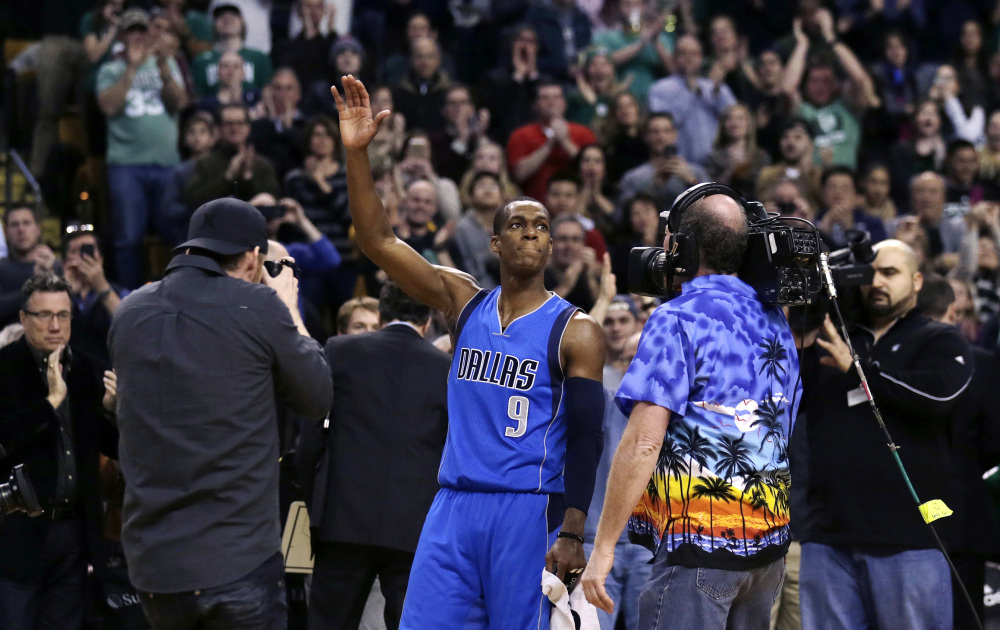 Dallas Mavericks guard Rajon Rondo waves to fans and photographers after a video presentation of his career with the Boston Celtics, during a break between the first and second quarters of Friday night's game in Boston. Rondo scored 29 points in his first game at the TD Garden since he was traded to Dallas last month.