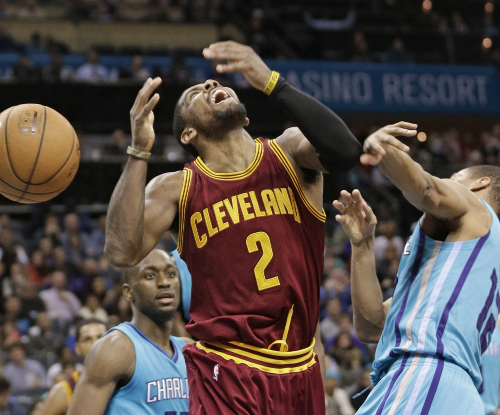 Cleveland's Kyrie Irving is fouled by Charlotte's  Gary Neal during the second half of Friday's game in Charlotte. The Cavaliers won despite being without LeBron James.