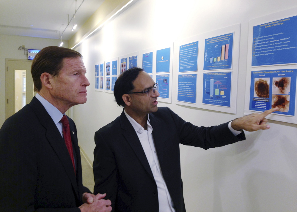 Anil Diwan, right, president and chairman of NanoViricides, describes the company's progress on an Ebola cure to U.S. Sen. Richard Blumenthal, D-Conn.