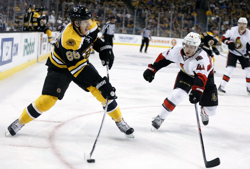 Boston Bruins' Kevan Miller takes a shot as Ottawa Senators' Jean-Gabriel Pageau defends during the second period of an NHL hockey game in Boston, Saturday, Jan. 3, 2015.