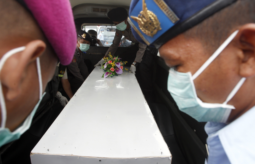 Indonesian military personnel load a coffin containing the body of a victim of AirAsia Flight 8501 onto an ambulance upon arrival at Juanda Naval Airbase in Surabaya, East Java, Indonesia.