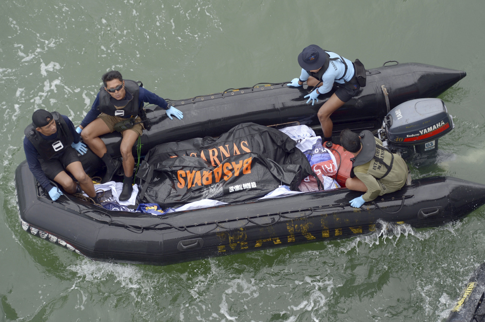 Indonesian Navy personnel carry a plastic bag containing the dead body of a passenger of AirAsia Flight 8501 at sea off the coast of Pangkalan Bun, Indonesia.