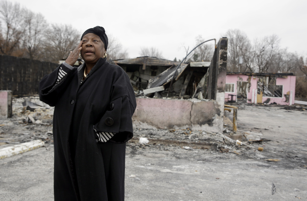 Juanita Morris wipes away a tear outside the remains of her business in Dellwood, Mo., a town next to Ferguson. Juanita's Fashions R Boutique was destroyed in rioting on Nov. 24, but money raised from a crowd-funding website will help her rebuild.