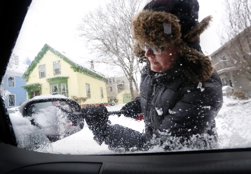 JAN. 4: Katie Benedict of Portland clears snow and ice from her vehicle after an overnight snowstorm. Mainers spent that Sunday shoveling out from a storm that dropped between 4 and 6 inches in most areas.
