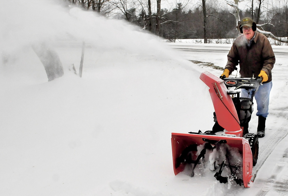 Ken Tozier uses his snowblower to clear off the three inches of snow off his driveway before freezing rain developed at his home in Unity on Sunday.  David Leaming/Staff Photographer