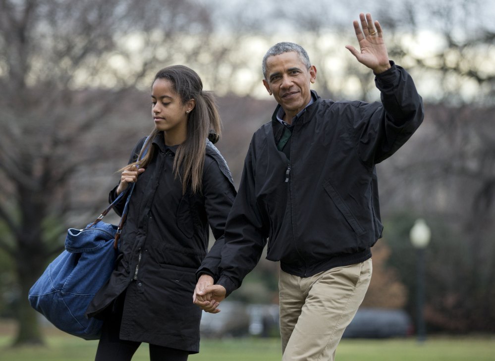 The Associated Press President Barack Obama with his daughter Malia Obama, waves as they arrive at the White House in Washington on Sunday from a family vacation in Hawaii.