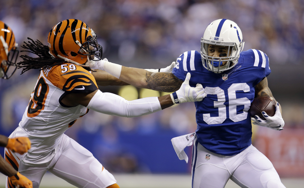 Indianapolis Colts running back Dan Herron runs against Cincinnati Bengals outside linebacker Emmanuel Lamur in the first half Sunday in Indianapolis. The Colts won, 26-10.