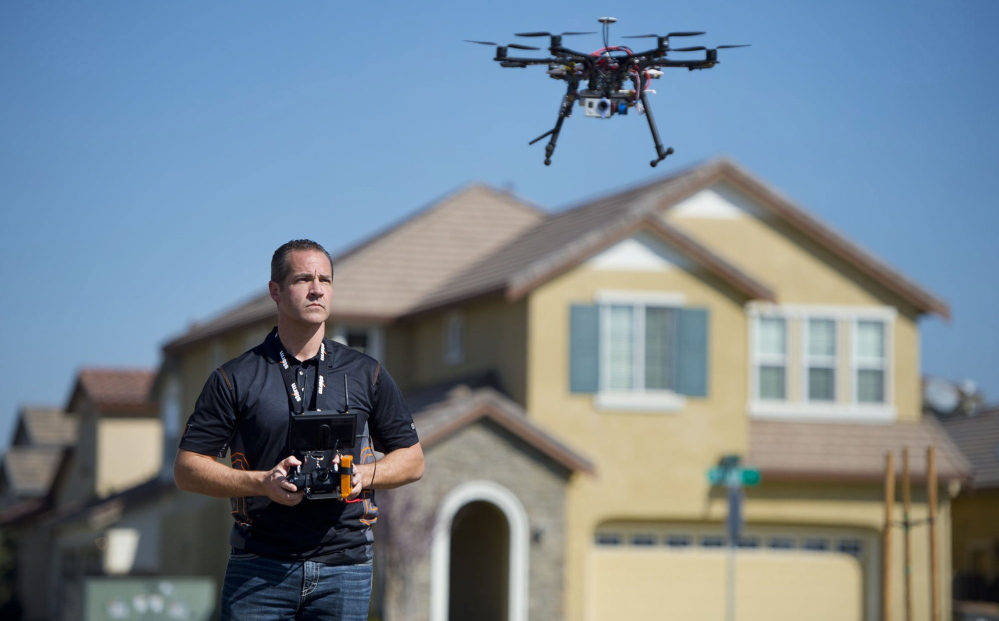 A real estate agent uses a helicopter drone to take video of a Sacramento, Calif., home. An FAA ban on the commercial use of drones is hard to enforce.