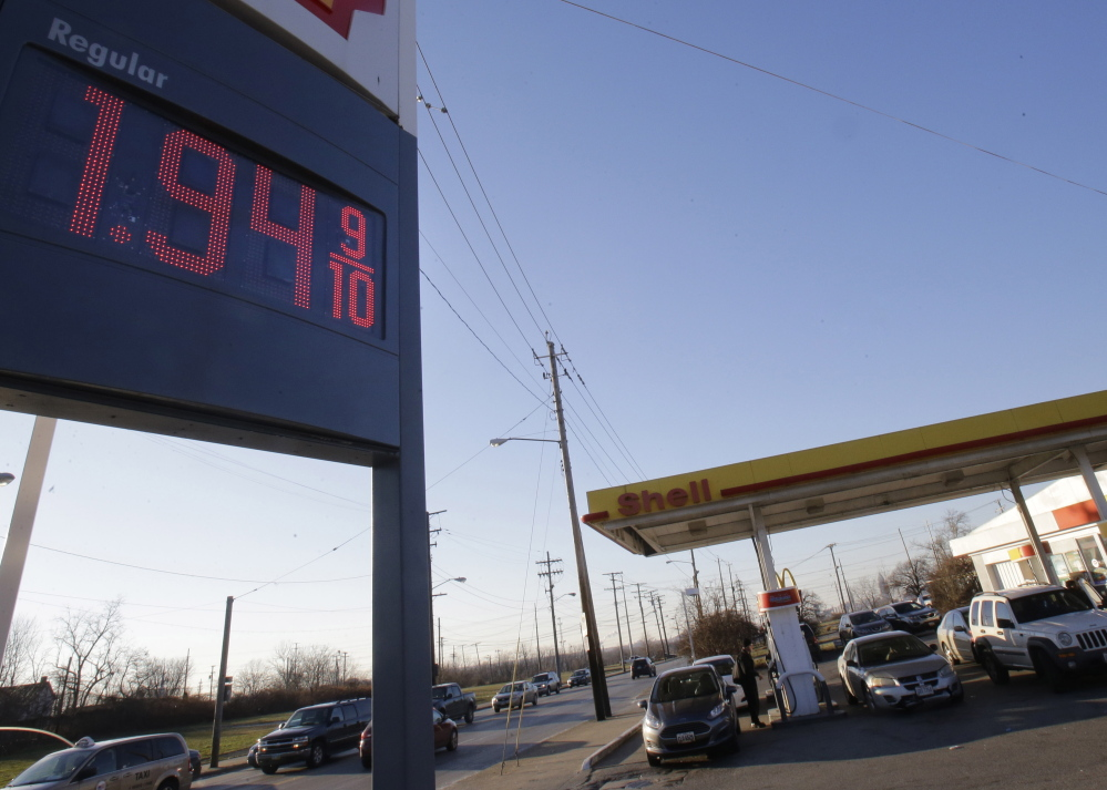 A gas station in Cleveland advertises a price of $1.94 per gallon. The price of oil plunged Monday and dipped below $50 a barrel for the first time in more than five years.