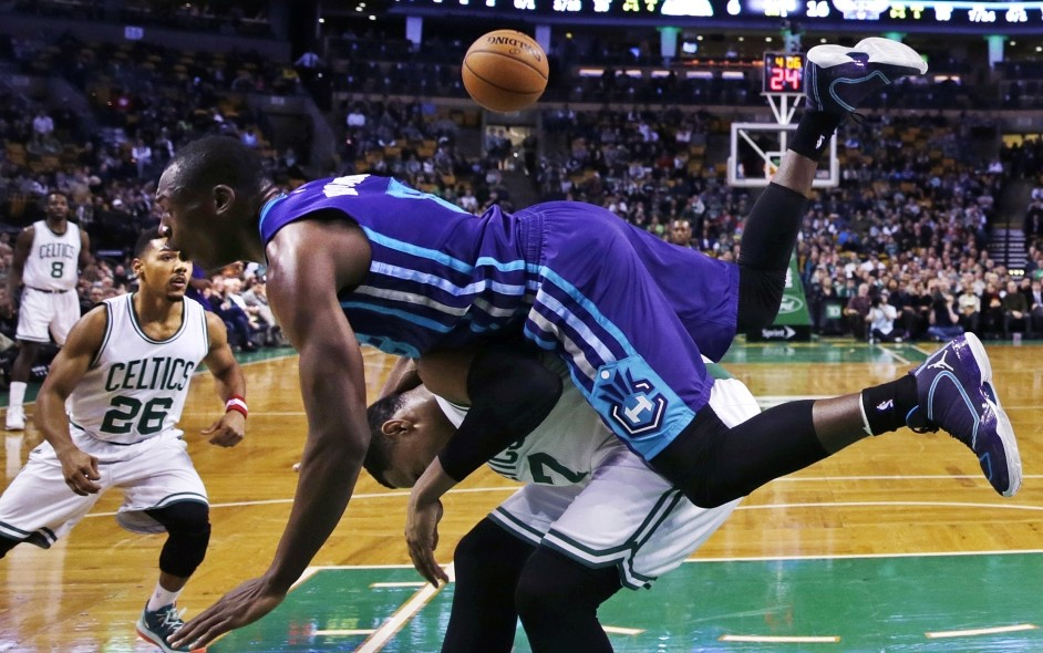 Charlotte Hornets center Bismack Biyombo tumbles over Boston Celtics forward Jared Sullinger on a rebound during the first quarter of Monday night's game in Boston.