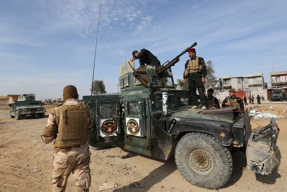 In this Monday, photo, Iraqi security forces deploy in a military operation to regain control of the villages around the town of Beiji, some 250 kilometers (155 miles) north of Baghdad, Iraq.