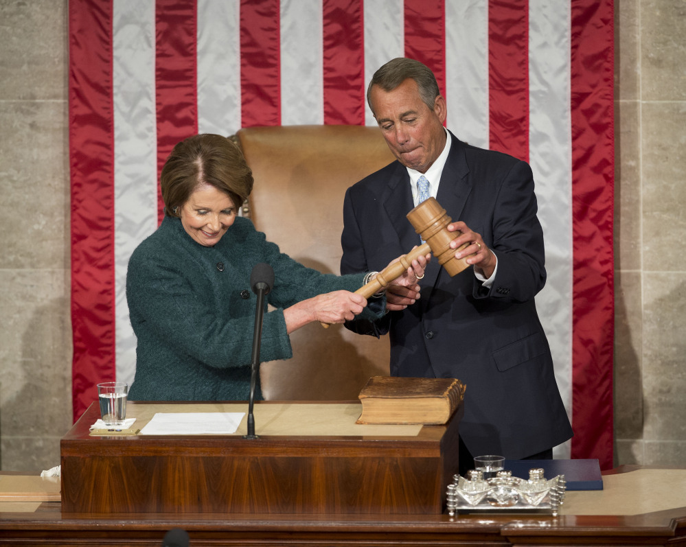 House Speaker John Boehner of Ohio is handed the gavel from House Minority Leader Nancy Pelosi of California on Tuesday on Capitol Hill in Washington after being re-elected for a third term to lead the 114th Congress, as Republicans assume full control for the first time in eight years.