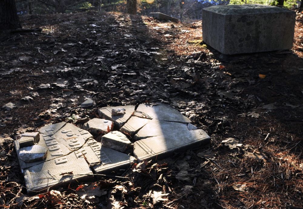 A cracked tombstone on the ground and the base of a four-sided obelisk are in the Edgecomb cemetery in Gardiner.