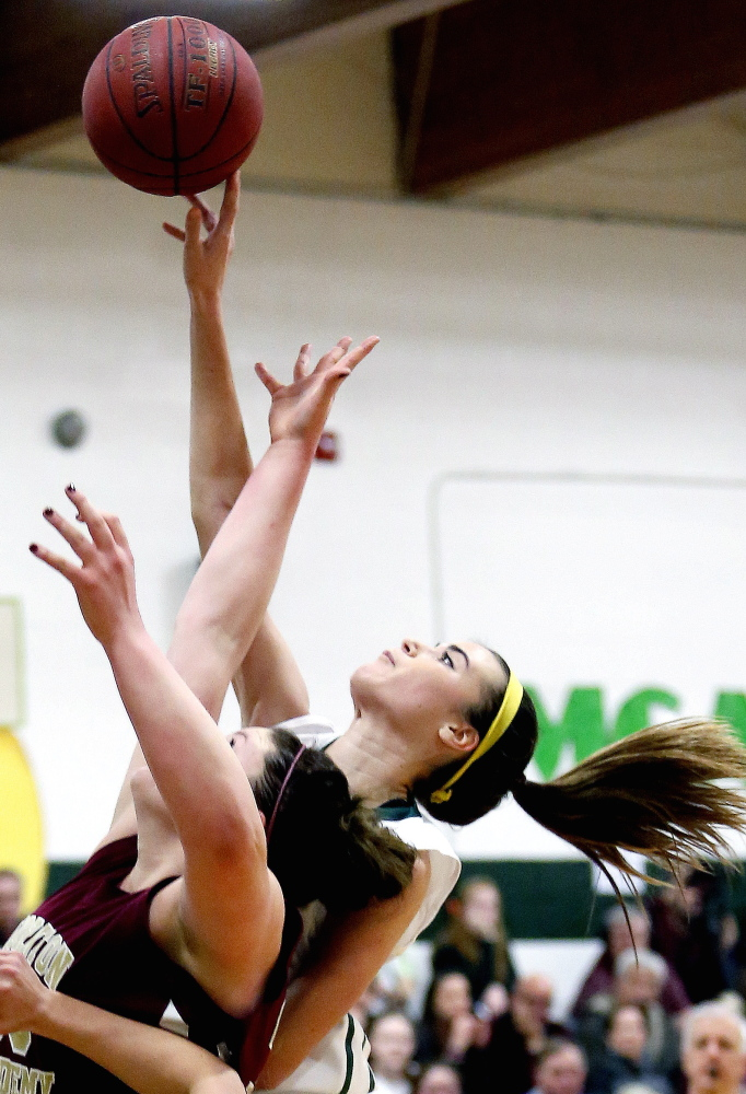 McAuley's Margaret Hatch gets her finger on the ball just over the outstretched arms of Thornton Academy's Victoria Lux during the second half of a girls' high school basketball game Tuesday.