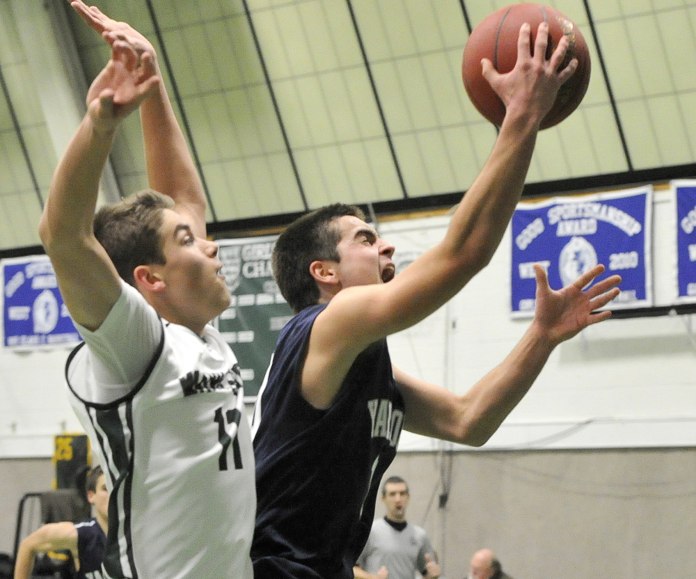 Cody Clark of Yarmouth slips past Milo Belleau of Waynflete for a layup Tuesday during the game between unbeaten Western Maine Conference teams. Belleau scored 17 points to lead the Flyers to a 53-43 victory.