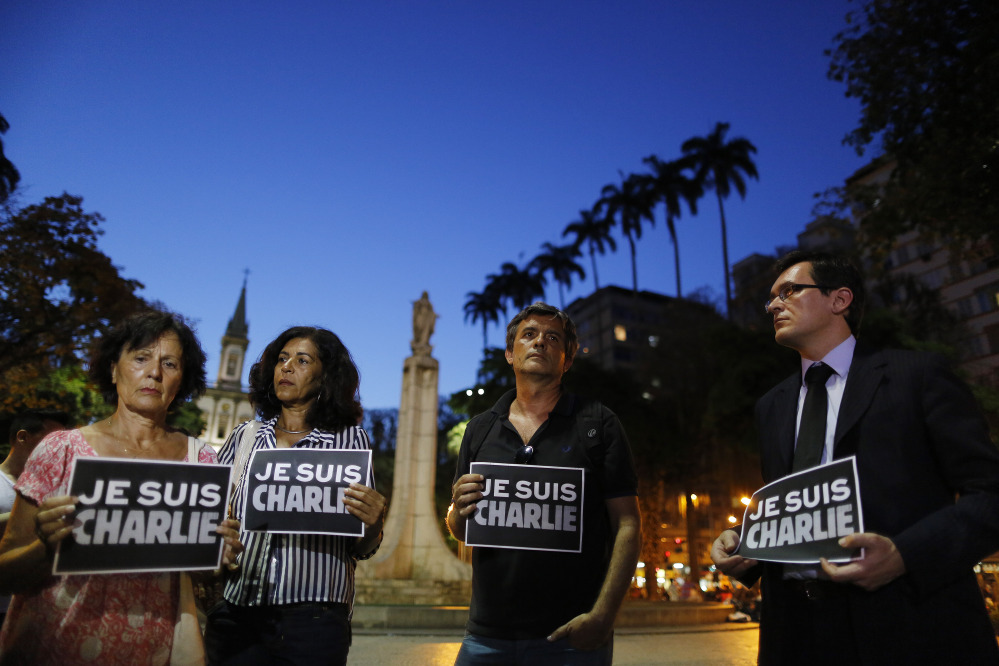 "People in Rio de Janeiro, Brazil, hold signs that read in French ""I am Charlie,"" in solidarity with those killed Wednesday at the Paris offices of the weekly newspaper Charlie Hebdo. Masked gunmen stormed the offices of the satirical newspaper, which caricatured the Prophet Muhammad."