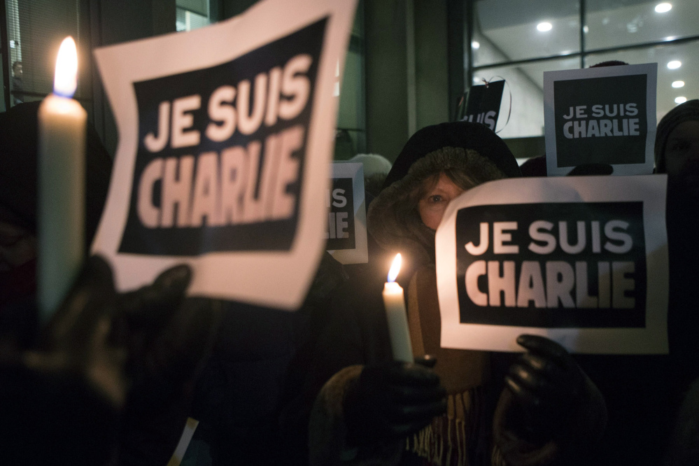 "People gather outside the French Consulate in Toronto on Wednesday in response to the shootings earlier in the day at Charlie Hebdo Magazine in Paris. The writing on the signs reads ""I am Charlie."""