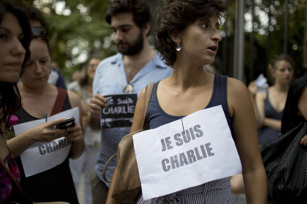 "People in Buenos Aires, Argentina, stand outside France's embassy wearing signs that read in French ""I am Charlie,"" in solidarity with those killed in Wednesday's attack at the Paris offices of the weekly newspaper Charlie Hebdo."