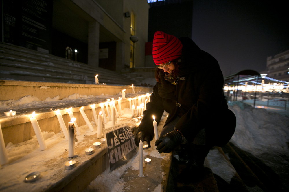 "A woman in Pristina, Kosovo, lights a candle near a sign that reads in French ""I am Charlie"" during a demonstration in solidarity with those killed in Wednesday's attack at the Paris offices of Charlie Hebdo."