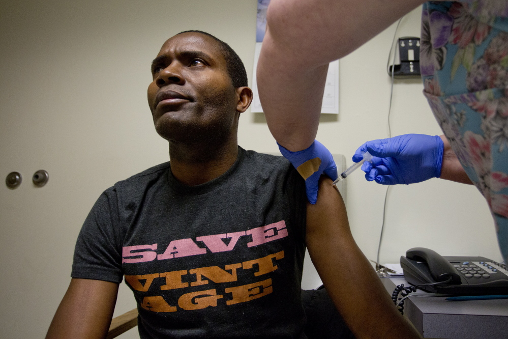 Susan Huff, vaccines manager at the Portland Community Health Center, administers a flu shot Wednesday to patient Bruno Mbango Enyaka, 41, at the Park Street clinic. No flu cases have been reported at the center so far this season.