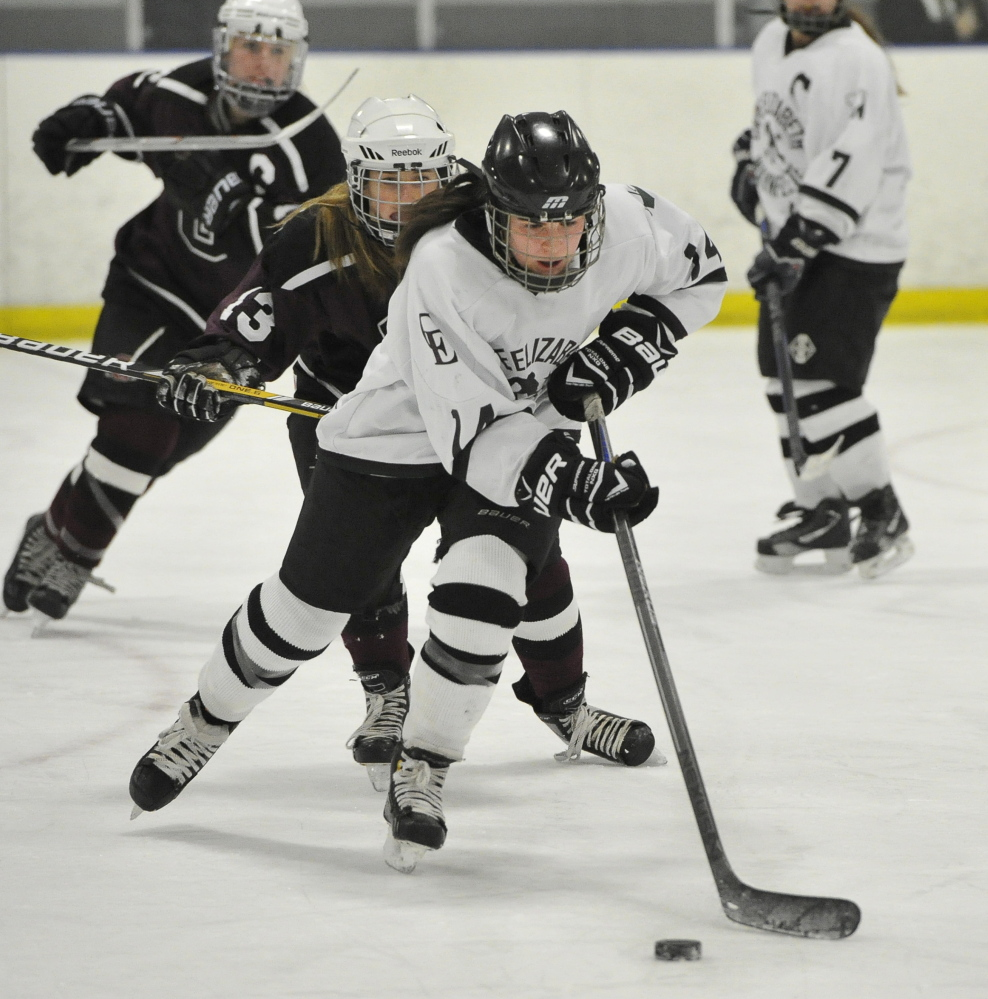 Kate Ginder of Cape Elizabeth/Waynflete/South Portland pushes the puck ahead of Greely's Faith Price in Wednesday's game. Greely improved to 10-2.
