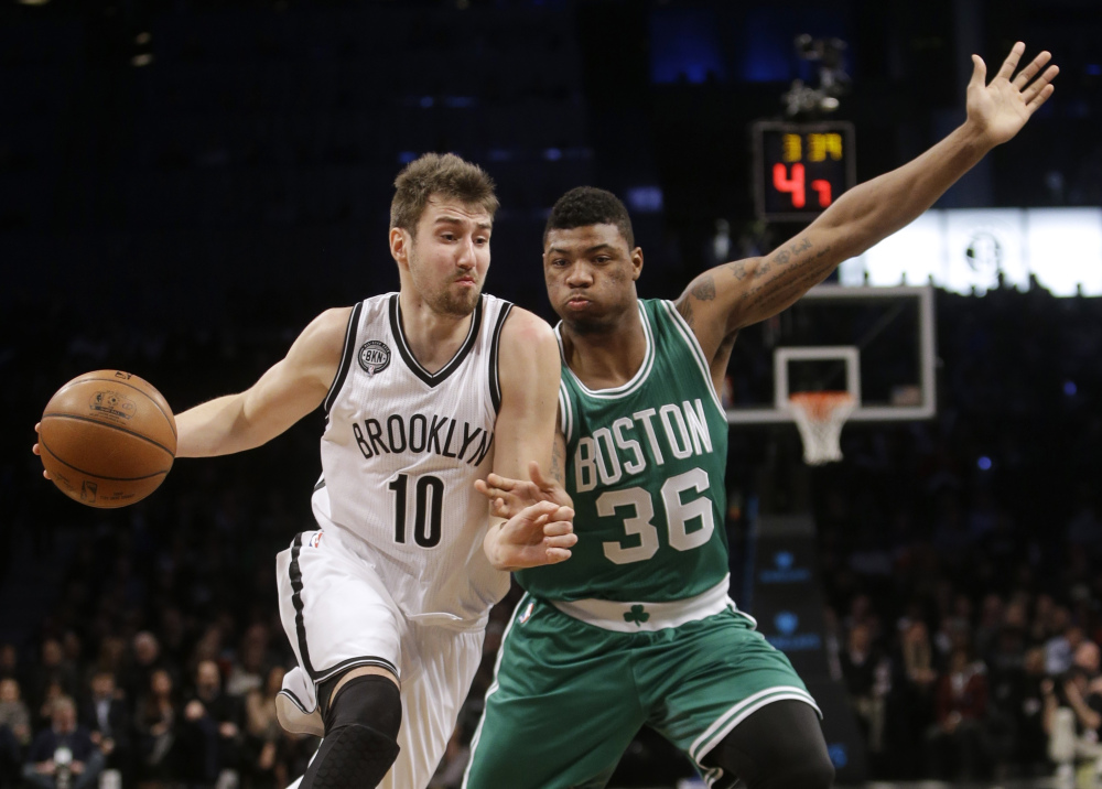 The Brooklyn Nets' Sergey Karasev drives past the Celtics' Marcus Smart during the first half of Wednesday night's game in New York. The Celtics trailed by 11 points in the first half but gradually pulled ahead after halftime.