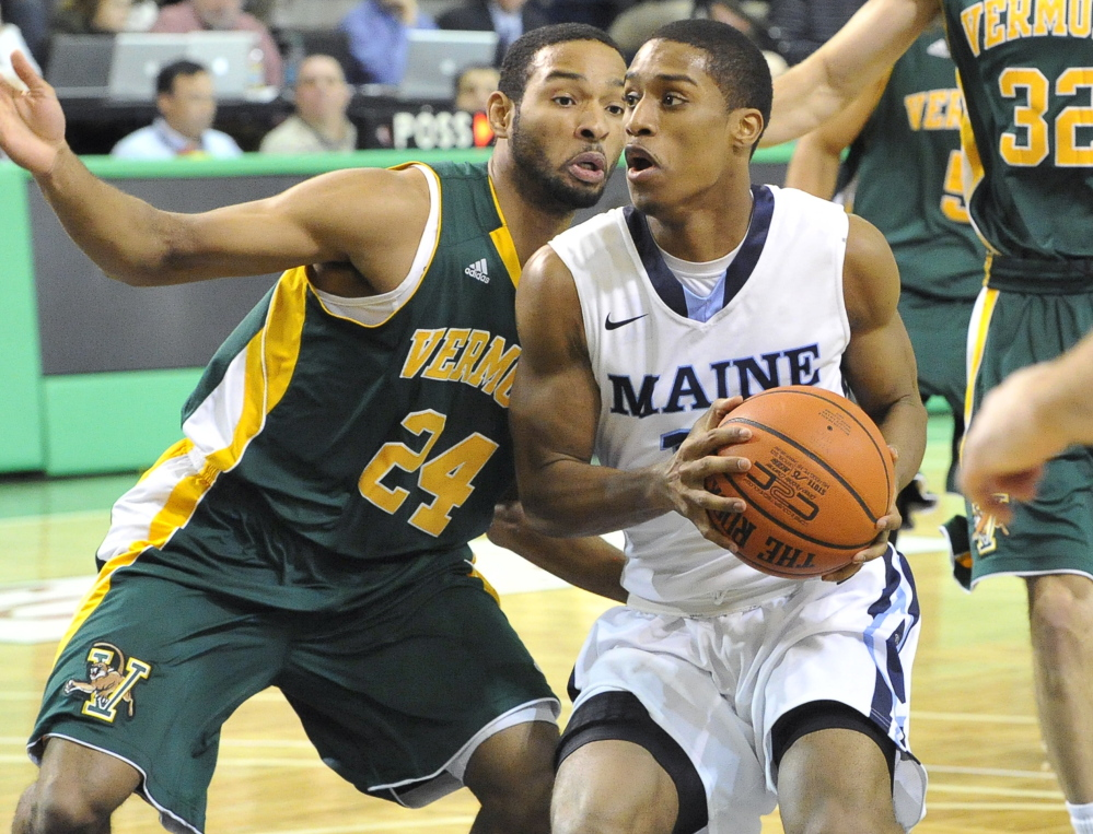 UMaine's Shaun Lawton looks for room against Dre Wills of Vermont on Wednesday night at the Portland Expo.