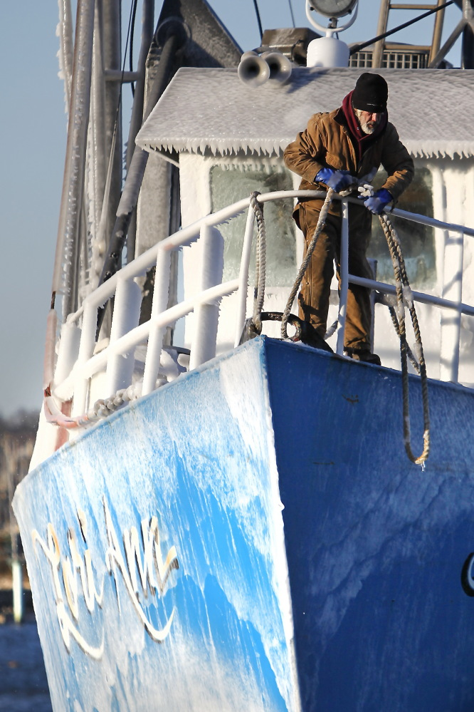 Jorge Furtado, first mate of the Lori Ann, prepares to tie the frozen clam ship to the dock in Fairhaven, Mass., on Thursday after arriving from a sea voyage, as frigid temperatures blanket the area.