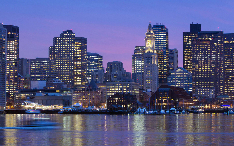 An illuminated Boston skyline shimmers off the waters of Boston Harbor. The U.S. Olympic Committee on Thursday announced that Boston had been chosen as the city that will represent the United States in bidding for the 2024 Games.  Associated Press file photo
