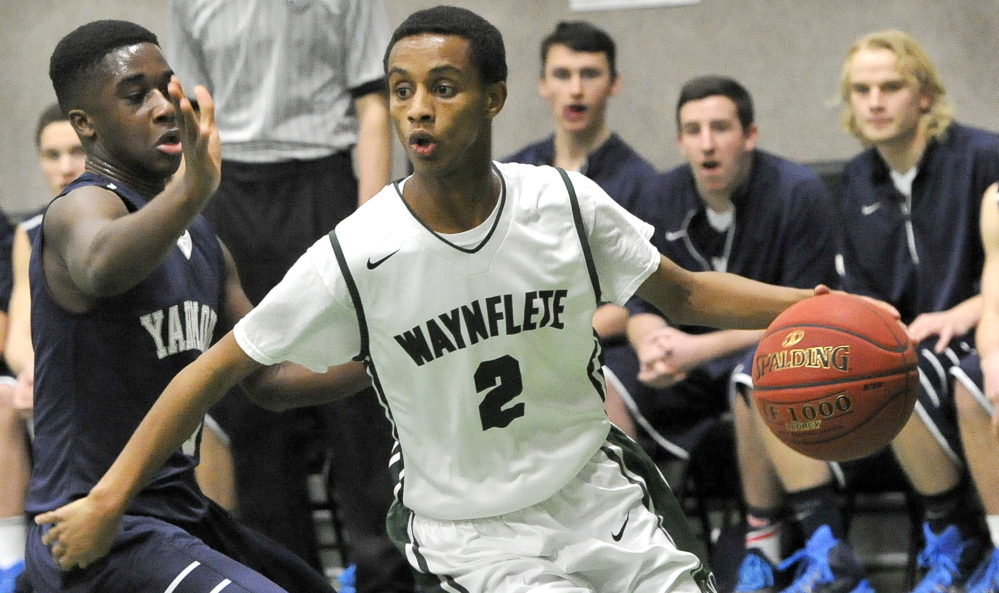 Waynflete's Abel Alemayo drives around Yarmouth's Musseit M'Bareck, left, during the Flyers' 53-43 win at  home Tuesday.
