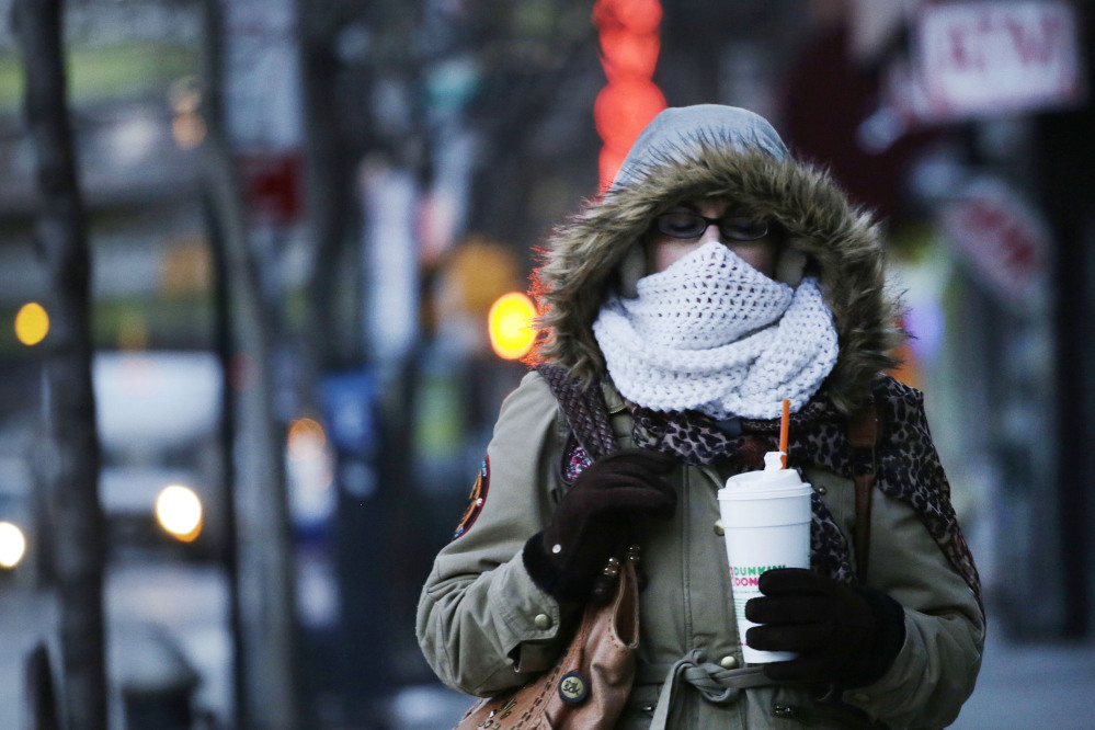 A New Yorker clutches a foam cup as she makes her way down a chilly street Thursday shortly before New York Mayor Bill de Blasio announced a ban on foam containers.