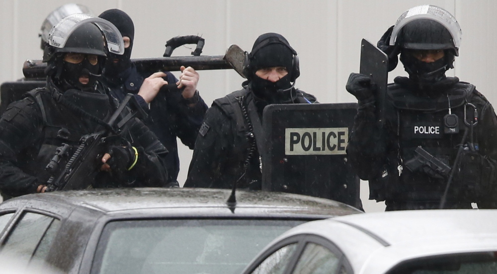 French police are seen at the scene of a shooting in Montrouge near Paris on Thursday. A policewoman was killed in a shootout, triggering searches in the area as the manhunt widened for two brothers suspected of killing 12 people.