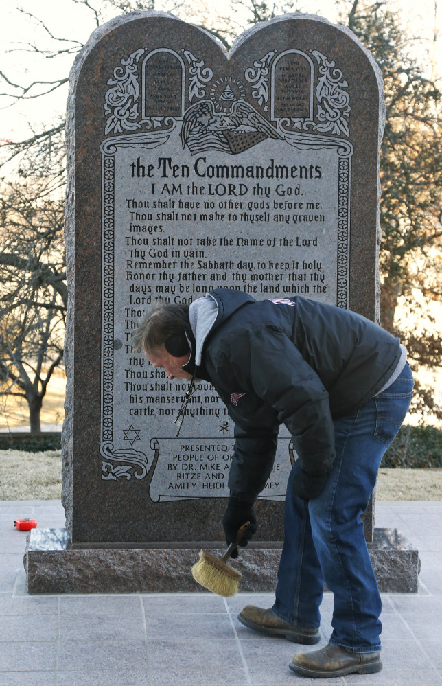 Mike Sanford, who placed the foundation for the Ten Commandments monument, sweeps in front of the replacement after it was installed at the state Capitol in Oklahoma City on Thursday. Someone crashed a car into the original monument.