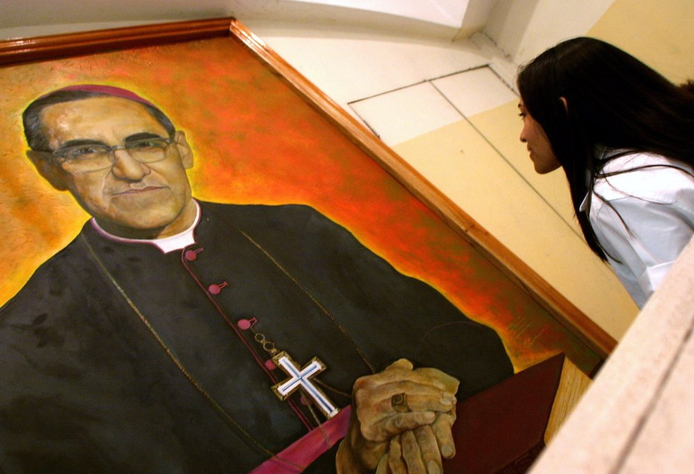 A woman views an image of Archbishop Oscar Romero, who was gunned down while celebrating Mass on March 24, 1980. Avvenire, a newspaper of the Italian bishops' conference, reports that Romero has been designated a martyr.