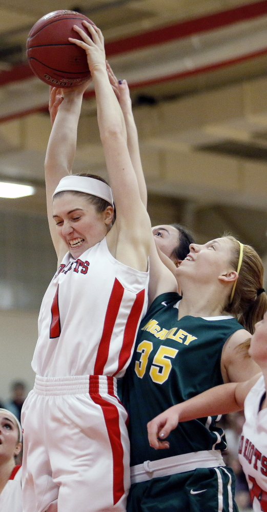 Paige Carter of South Portland controls the inside to haul down a rebound in front of Emily Weisser of McAuley. Despite the loss, the Red Riots held a 33-19 advantage on the boards.