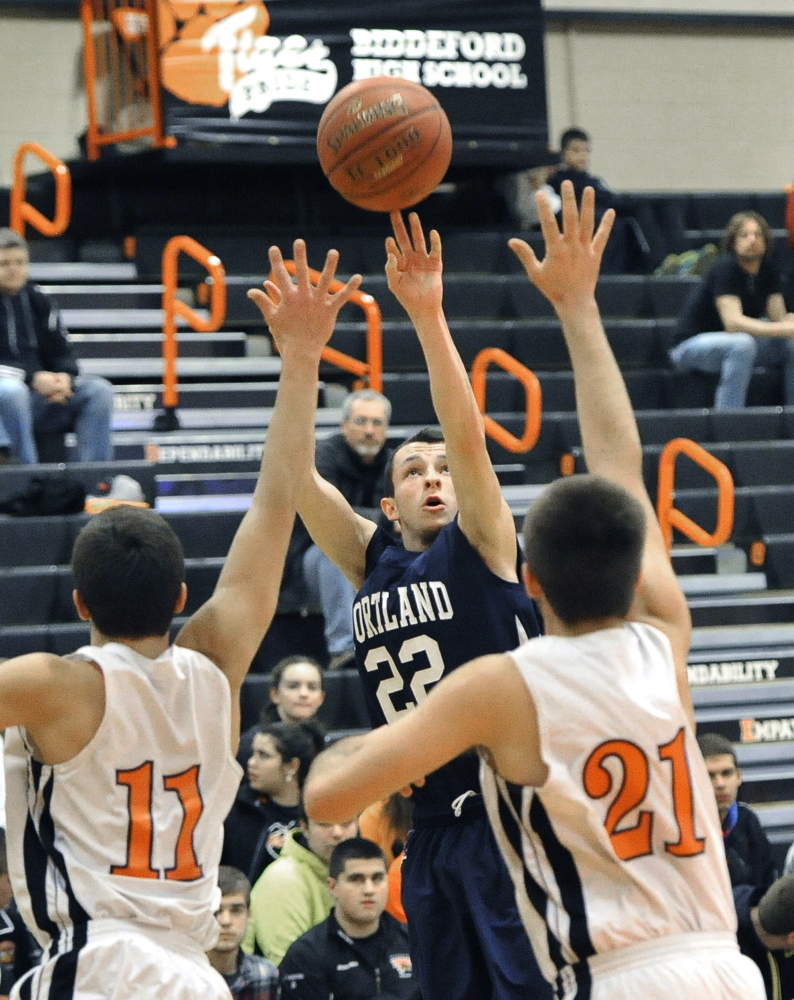 Liam Densmore, who finished with 17 points for Portland, lofts a jumper between Patrick Pearl, left, and Jason Vadnais of Biddeford during Portland's 67-33 victory Friday night at Biddeford High.