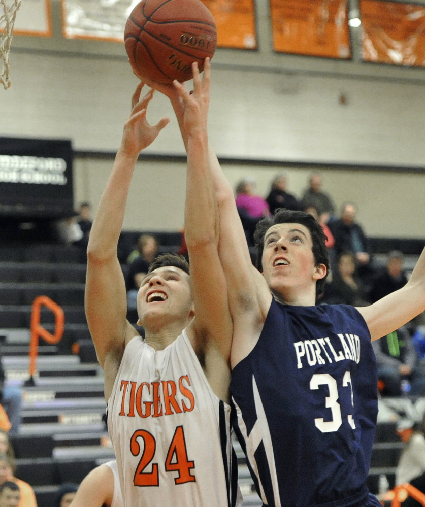 Ben Griffin of Portland, right, attempts to reach over Codie Ramos of Biddeford for a rebound. Portland remained undefeated in nine games and dropped the Tigers to a 1-9 record.