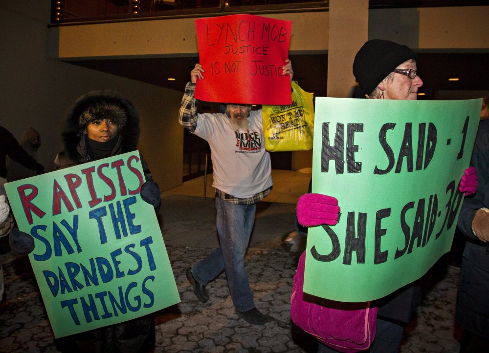 A Bill Cosby supporter (center) marches among protesters demonstrating outside the Hamilton Place Theatre before a performance by Cosby in Hamilton, Ont., on Friday night.