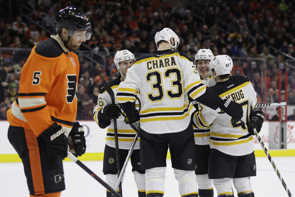 Torey Krug, 47, David Pastrnak, 88, Zdeno Chara, 33, and David Krejci celebrate a first-period goal Saturday as Philadelphia's Braydon Coburn skates by in Philadelphia.