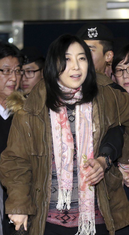 Shin Eun-mi, center, arrives at the Incheon International Airport for departure Saturday. Shin is involved in the latest in a series of cases that critics say infringe on the country's freedom of speech because she complimented North Korea.
