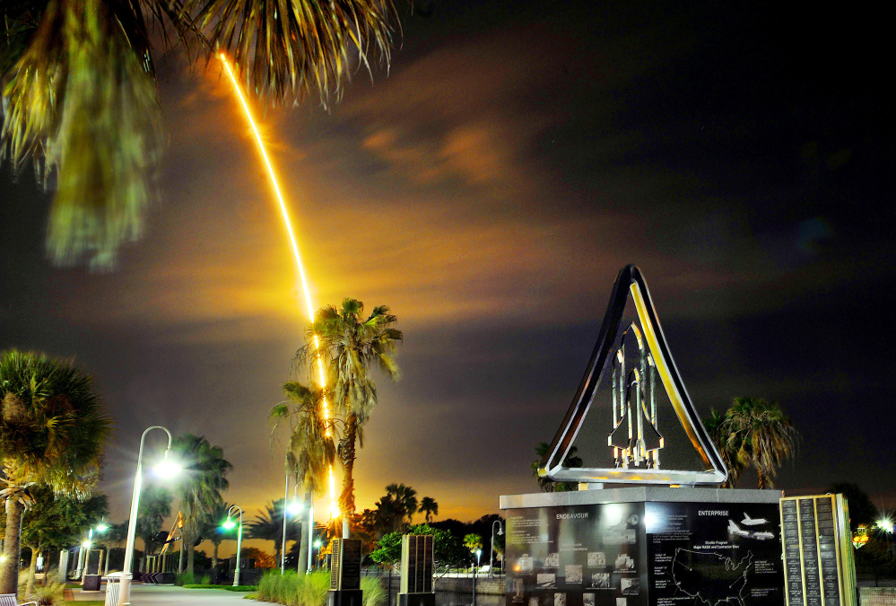 A SpaceX Falcon rocket with a Dragon cargo capsule aboard lights up the sky after liftoff from the Cape Canaveral Air Force Station launch complex as it streaks past a space shuttle monument in Titusville, Fla., early Saturday.
